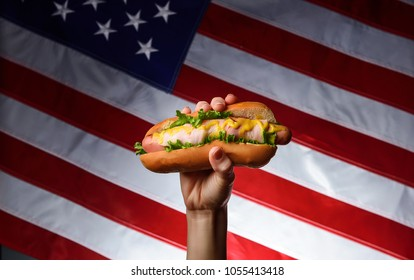 classic american hot dog in hand on american flag background