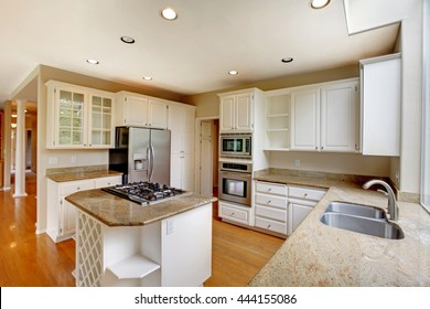 Classic American kitchen interior with white cabinets and built-in stainless steel fridge. View of living room with white columns.
