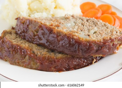 Classic American meatloaf made with ground beef oatmeal onions and a ketchup brown sugar and mustard glaze served with mashed potatoes and carrot coins