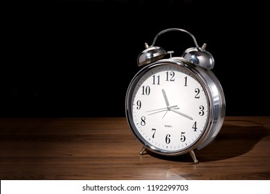 Classic analog alarm clock on wood, dark background with copy space