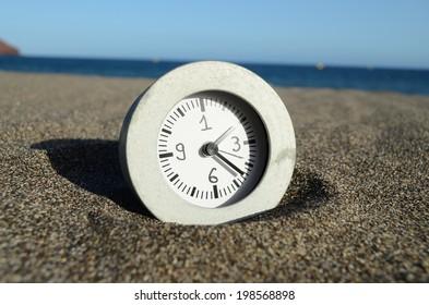 Classic Analog Clock In The Sand On The Beach Near The Ocean
