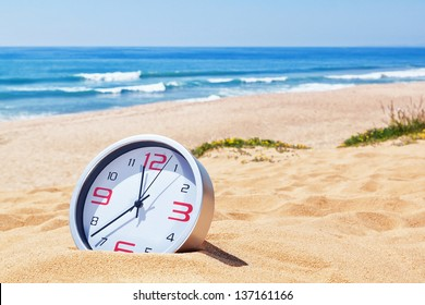 Classic analog clocks in the sand on the beach near the sea. For the holidays.