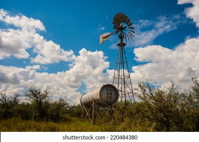 Classic antique Farm Windmill with clouds surrounding it.