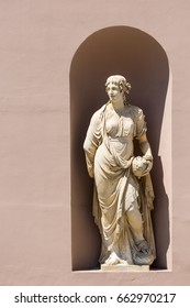 Classic antique stone statue of a woman in a public wall in Triest, Italy