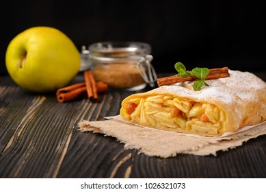 Classic apple strudel on a wooden board. Apfelstrudel