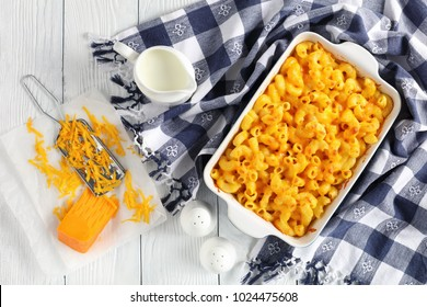 classic Baked Homemade Macaroni and Cheese in baking dish  with kitchen towel and grated cheddar cheese on paper on wooden table, view from above