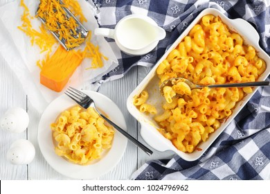 classic Baked Homemade Macaroni and Cheese in baking dish and on plate with fork. grated cheddar cheese  and jug with fresh cream on wooden table, view from above, close-up