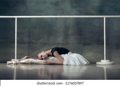 The classic ballet dancer in white tutu posing at ballet barre on studio background. Young teen before dancing. Ballerina project with caucasian model. The ballet, dance, art, contemporary