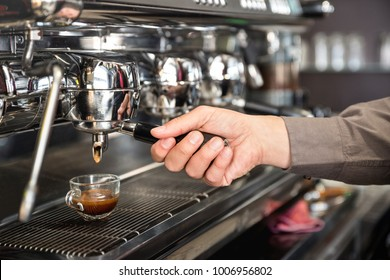 Classic barman hand preparing italian espresso at modern coffee bar machine in fashion cafeteria - Food and beverage concept with professional bartender at cafe stand working station