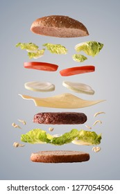 Classic beef burger with onion floating with ingredients broken down in parts on gray gradient isolated background. Front view. Vertical composition.