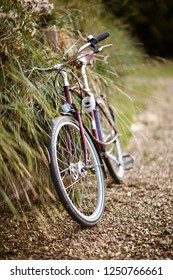 A classic bicycle leaning on a fence in a country lane