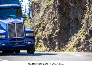 Classic big rig professional industrial grade American bonnet blue transportation semi truck tractor running on winding mountain road with rock wall on the side transporting commercial cargo