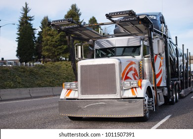 Classic big rig semi truck with square grille and two story compact car hauler semi trailer running on the road to unloading transporting to point of destination vehicles