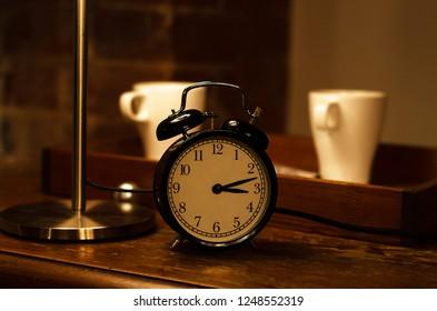 classic black alarm clock on wooden background