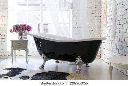 Classic black bathtub beside the window