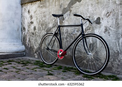 classic black bicycle on the streets of old city, grey concrete wall background