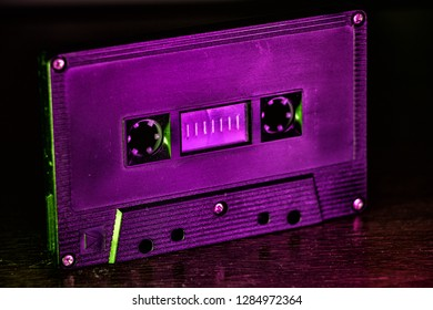 A classic black cassette tape on a table with purple and green light.