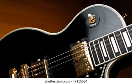 Classic black Les Paul style rock and roll or jazz guitar in soft spotlight. Stage or studio concept ready to perform.