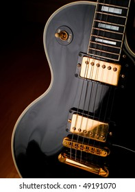 Classic black Les Paul style rock and roll guitar. Soft lighting on instrument for a stage or studio atmosphere.