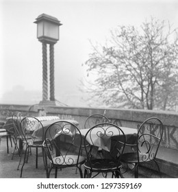 A classic black & white film photo of old style chairs on a foggy winter morning in Zagreb, Croatia