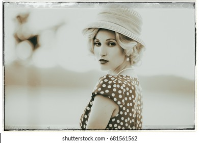 Classic black and white photo of seductive looking woman wearing vintage 1930s fashion. Standing in rural summer landscape.