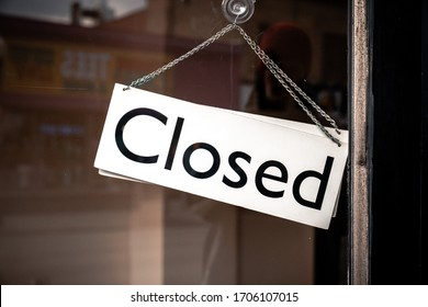 Classic black and white sign and chain hangs on an angle in a glass storefront or door due to the shop or retail business being closed during the COVID-19 outbreak and government stay at home orders.