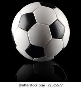 a classic black white soccer ball on black background