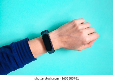 Classic blue fitness bracelet for sports training on a girl's hand on mint background. Selective focus.