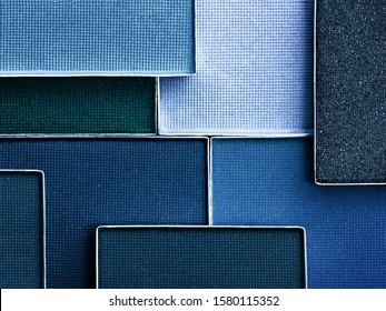 Classic blue palette of eye makeup. Color of the year 2020. Classic blue background. Cosmetics products background in trendy color scheme.