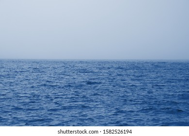 Classic blue sea and sky background. Cloudy horizon and fog over the sea waves, natural background. Fog sea classic blue color background. Classic blue background of sea with fog. Color trendy 2020.