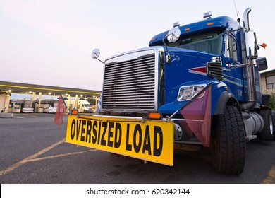 Classic blue truck with the sign oversized load on the truck stop on the background of a gas station with truck and buses. Front view opens up a powerful vehicle with a grille, the turned wheel.