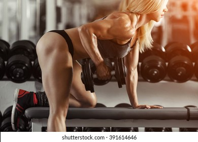 Classic bodybuilding. Muscular blonde fitness woman doing exercises in the gym. Fitness woman in the gym. Bodybuilder woman in the gym. Fitness woman with dumbbell.