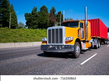 Classic bonnet legendary popular bright orange big rig semi truck with high exhaust pipes and chrome bumper and red corrugated container on flat bed semi trailer running on the road to destination