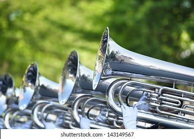Classic Brass band plays the musical in garden.Musician marching and holding instrument Ex.silver trumpet, brass tuba and other classical instrument at green music center. The Bran play by student.