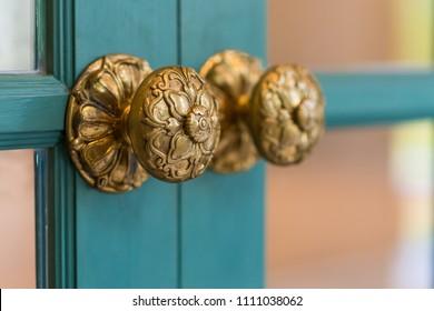 Classic brass door knob on green door vintage style
