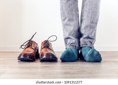 Classic brown men's brogues shoes and a man in blue socks. Men's stylish look.