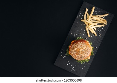 Classic burgers with becon, meat, cheese, onion, tomato and cheese and integral bun. On textured black board. Fried potatos. Flat lay.