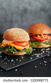 Classic burgers with becon, meat, cheese, onion, tomato and cheese and integral bun. On textured black board. Close up