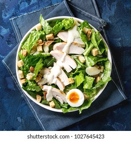 Classic Caesar salad with grilled chicken breast and half of egg in white ceramic plate. Served with croutons and dressing on cloth napkin over blue texture background. Top view, space. Square image