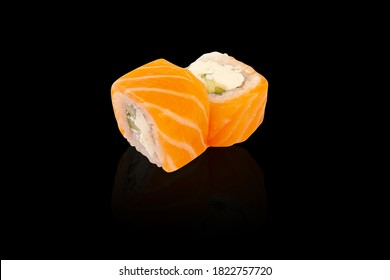 classic California roll with fish, salmon, avocado, cheese, and rice. Japanese cuisine. on a black background with reflection.