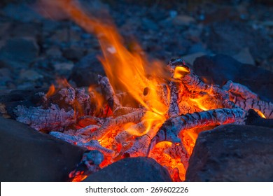 Classic camping campfire in rock fire ring at dusk closeup