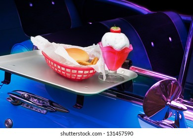 Classic car in drive-in with burger and milk shake