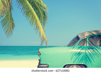 Classic car on a tropical beach with palm tree