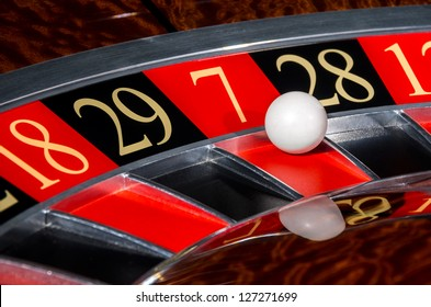 Classic casino roulette wheel with lucky red sector seven 7 and white ball