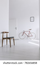 Classic chair in bright hall with red bike against wall with picture next to door