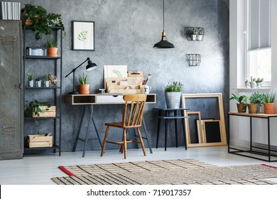 Classic chair at white desk against concrete wall in home office with plants