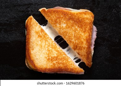 Classic cheese and ham toasted sandwich cut in half isolated on black cast iron griddle. Top view.