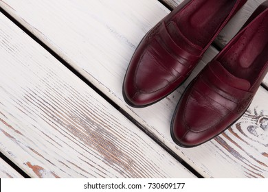 Classic cherry leather shoes. Pair of women's loafers on a rustic display of the store. Handmade footwear.