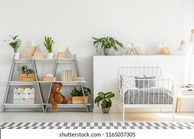 A classic child bedroom interior with simple, scandinavian style furniture and a gray wooden bookcase with a teddy bear