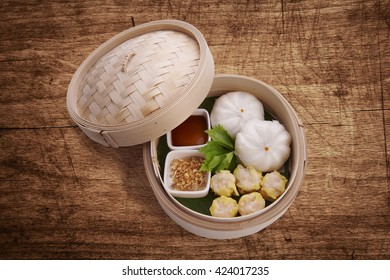 Classic Chinese style Canton cuisine - pork steamed dumpling or dim sum along with Chinese bun served in small steamer basket on wood background